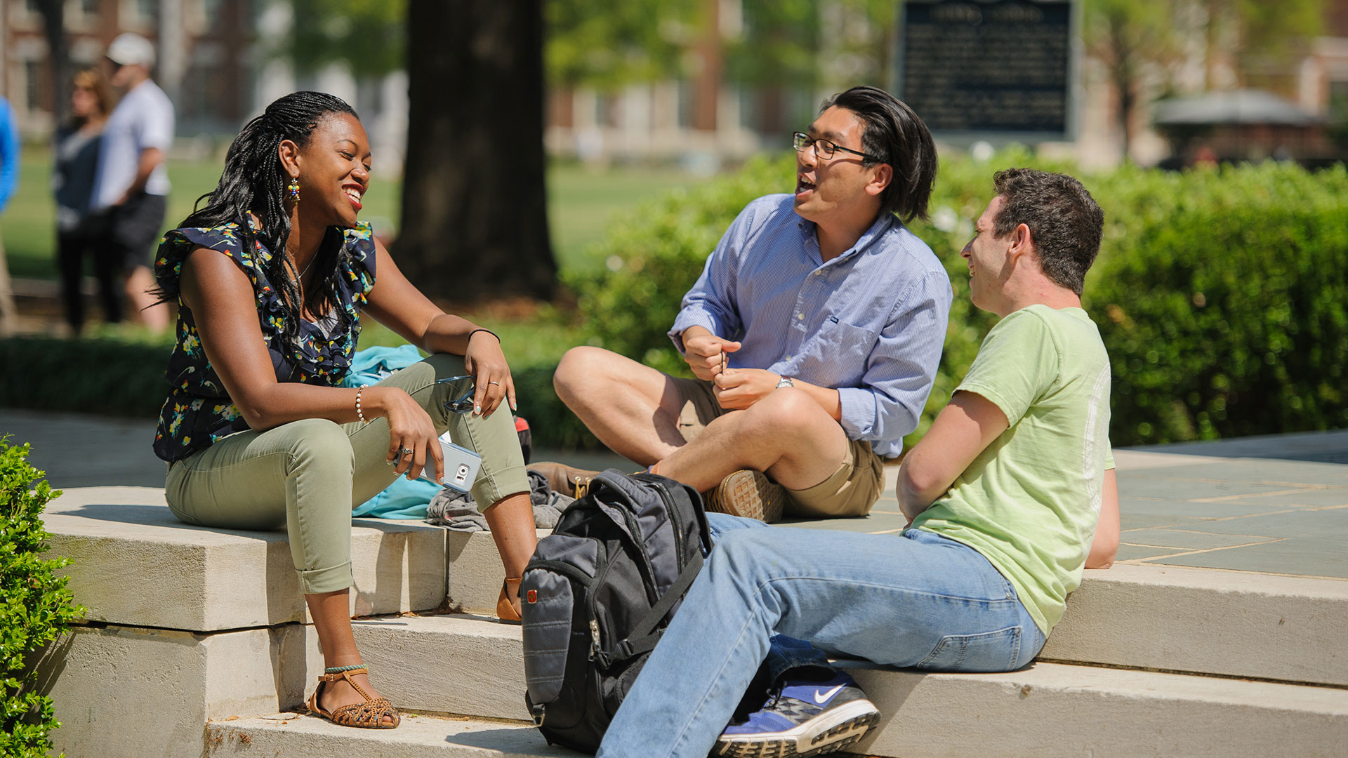 Three students laughing on the steps of Denny Chimes