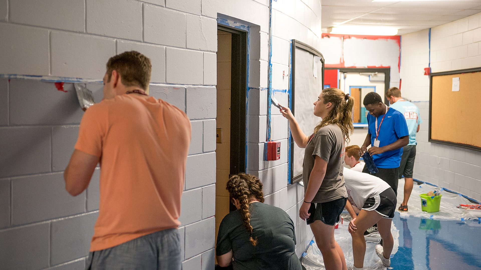 Students painting an elementary school's walls to help out