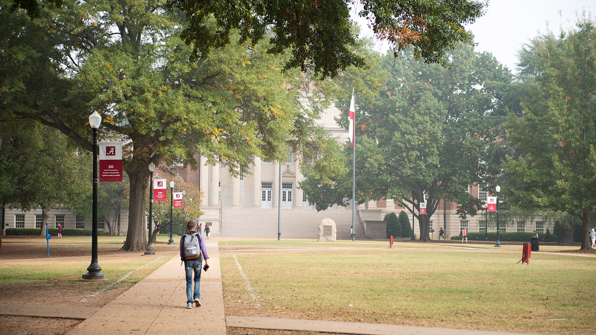 Next Story Image - Students walking on campus in the fall