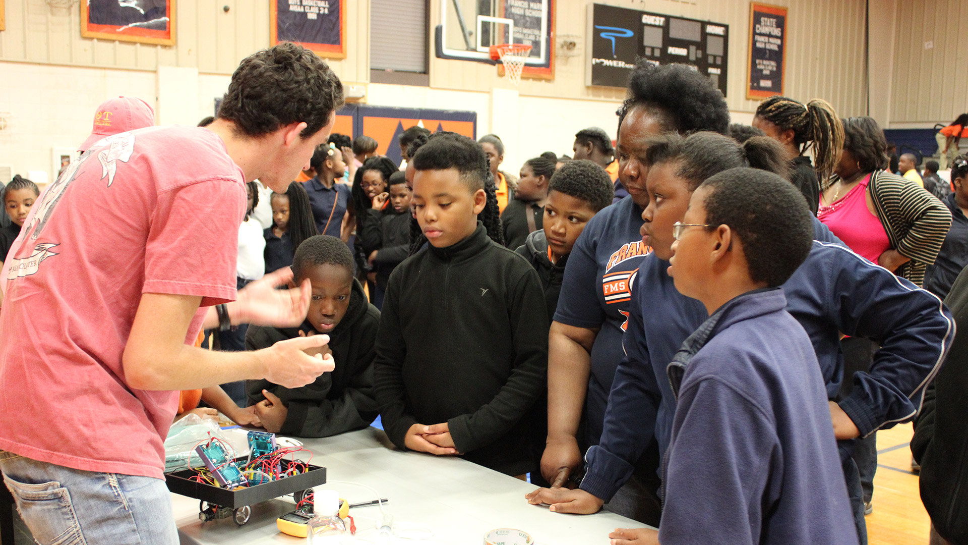 Story Image - A student showing off a fun engineering project to children in a gym