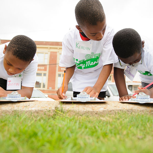 Three young boys writing outside.