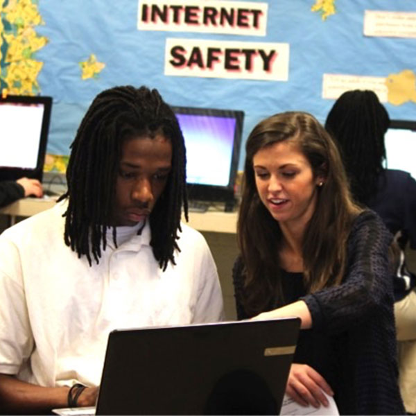 A UA student helps a high school student on a computer.