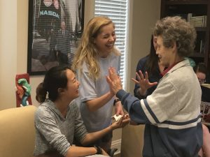 Three students laughing with an elderly Alzheimer patient as she gives one of them a high five