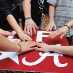 Multiple student hands touch red logo of Design for America.
