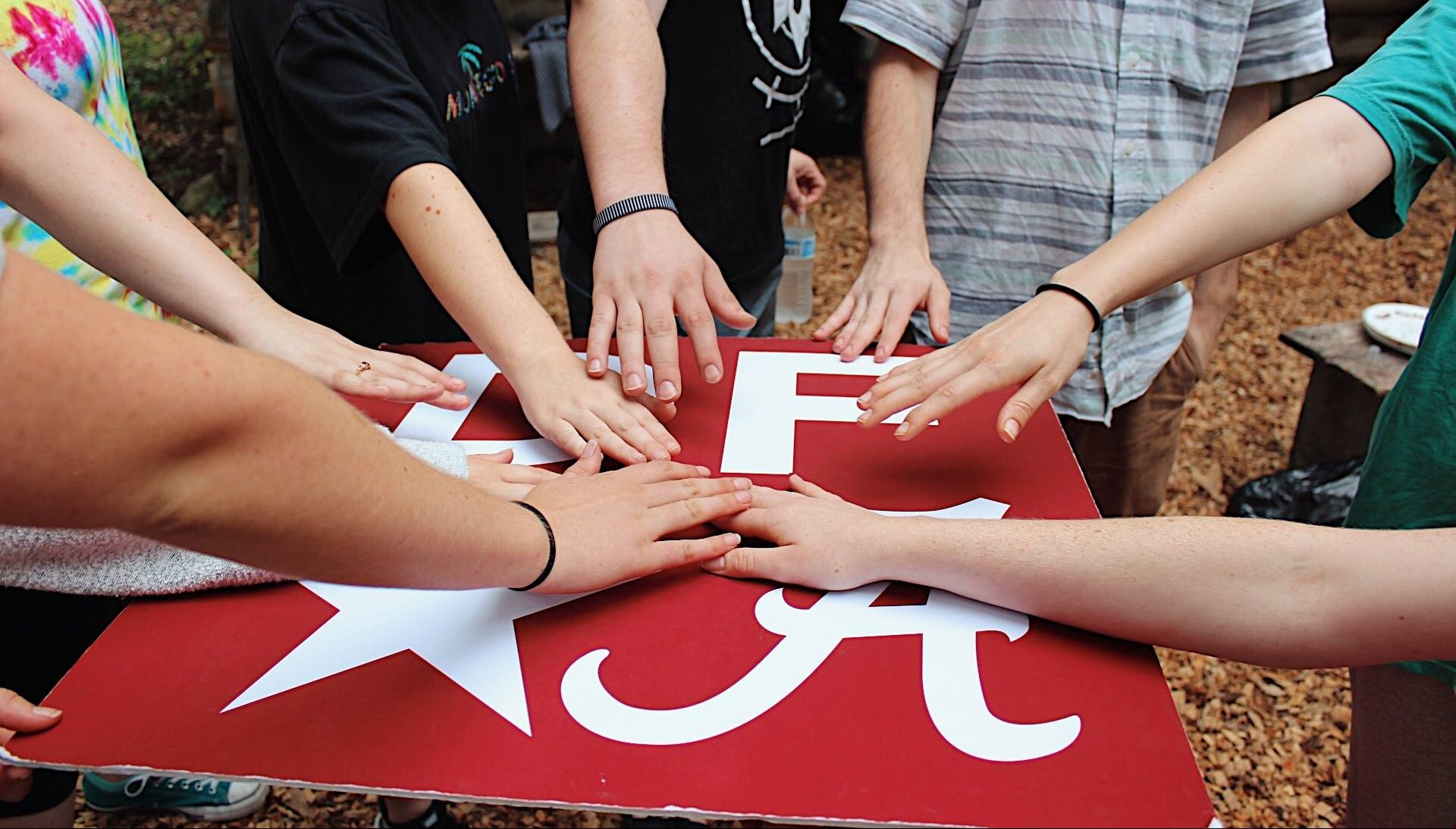 Story Image - Multiple student hands touch red logo of Design for America.