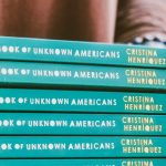 Student holding stack of books titled The Book of Unknown Americans