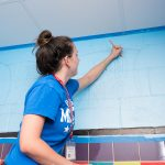 Honors Action Student tracing a mural