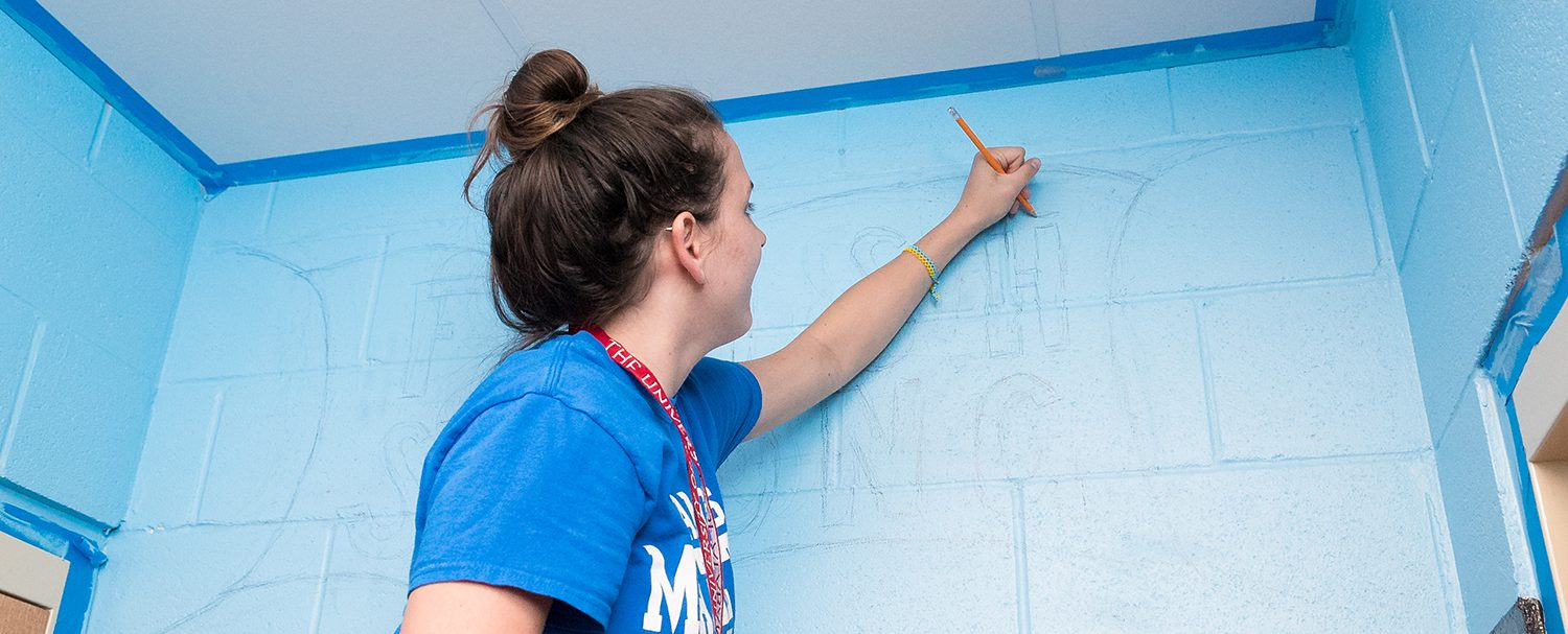 Story Image - Honors Action Student tracing a mural