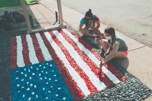 Students paint an American flag rock mural.